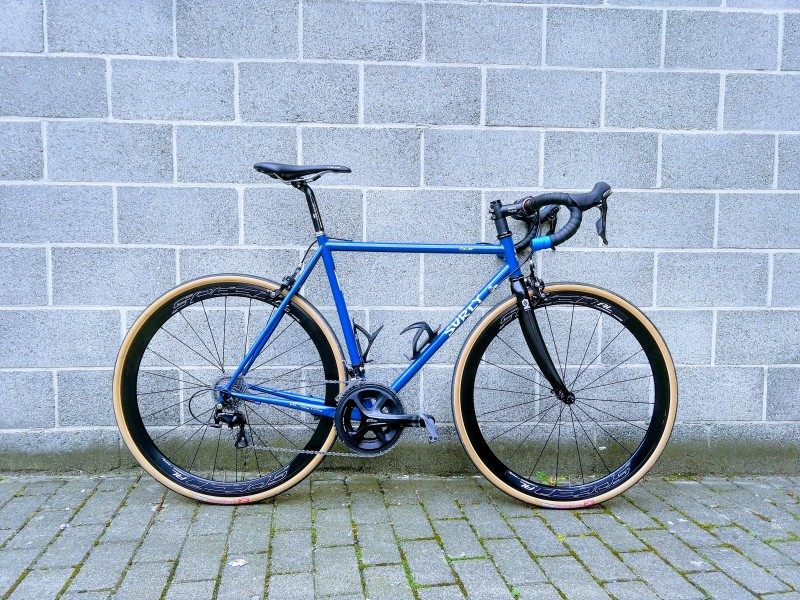 Right side view of a Surly Pacer road bike, blue, with a cinder block wall behind