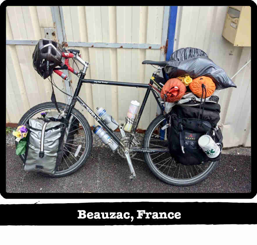 Left side view of a black Surly Long Haul Trucker bike with gear, leaning on a wall - Beauzac, France banner below image