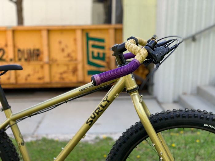 Side view of Corner Bar on bike with purple mountain grips on drops and gold bar tape on top, yellow dumpster in background