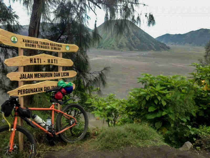 Left side view of an orange Surly Troll bike, leaning on sign, with a grass field and green mountains in the background