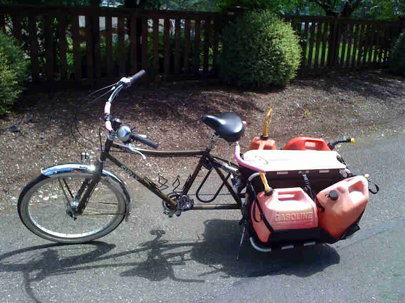 Left side view of a Surly Big Dummy bike, loaded with gas cans, parked on a paved street