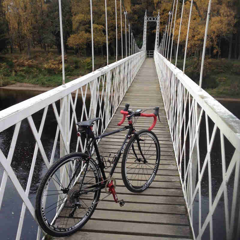 Rear right view of a black Surly Cross Check bike, parked on a trail bridge above a river, facing into the forest