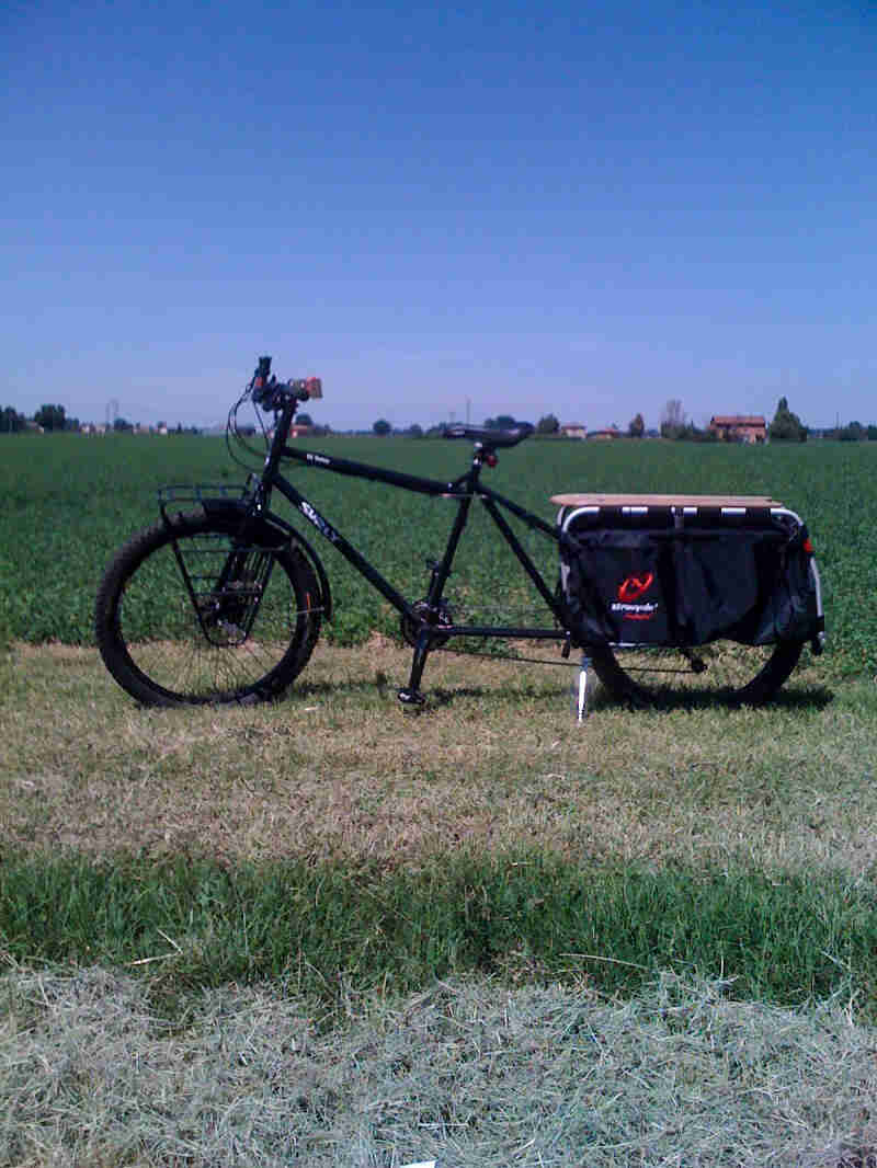 A Surly Big Dummy bike, black, parked in grass in front of a green field - left profile view
