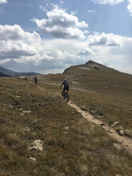 Rear view of cyclists riding up a narrow dirt trail, up a grassy hill, with blue sky and clouds above