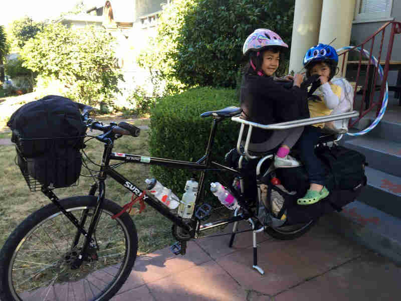 Left view of a Surly Big Dummy bike, black, with 2 small children in the rear rack, in front of a home