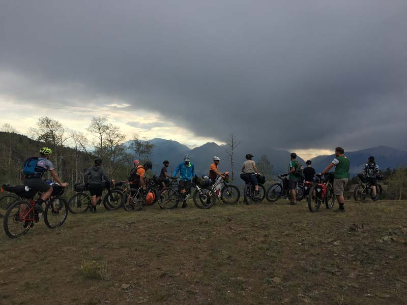 Cyclists lined up on a grassy plot, stare up at storm clouds above the mountains in the distance