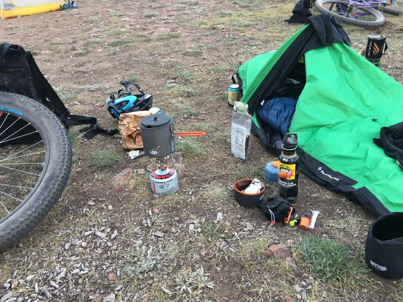 Camping gear laying on the ground, with bike laying near by