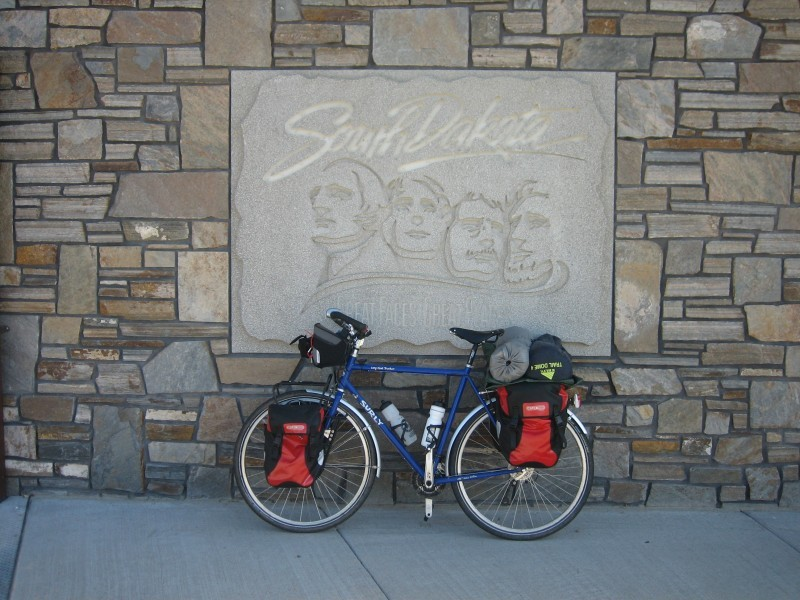 Left side view of a blue Surly Long Haul Trucker bike, loaded with gear, against a stone wall with a Mt. Rushmore sign