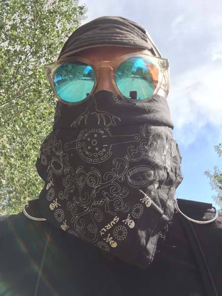 Front view of a person wearing a cap, sunglasses, and a black Surly bandana covering their face