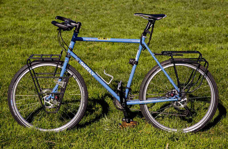 Left profile of a blue Surly bike with front and rear racks, standing in a green, grass field