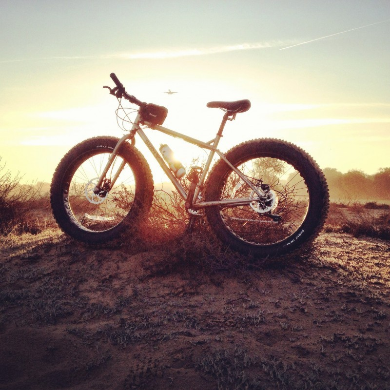 Left side view of a Surly fat bike, parked on a dirt mound, with the sun behind on the horizon and a plane flying over