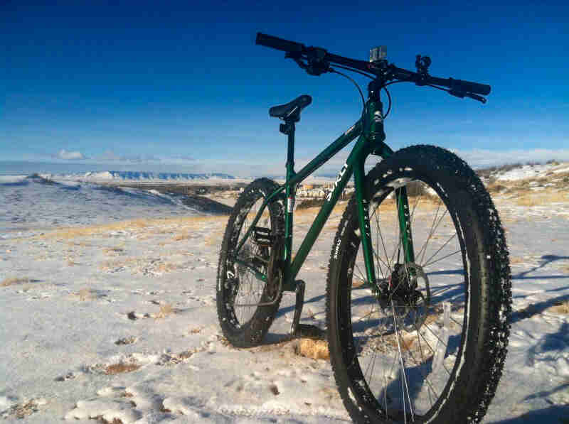 Front, right side view of a Surly bike, green, on snowy plains, with mountain in the background and blue sky above