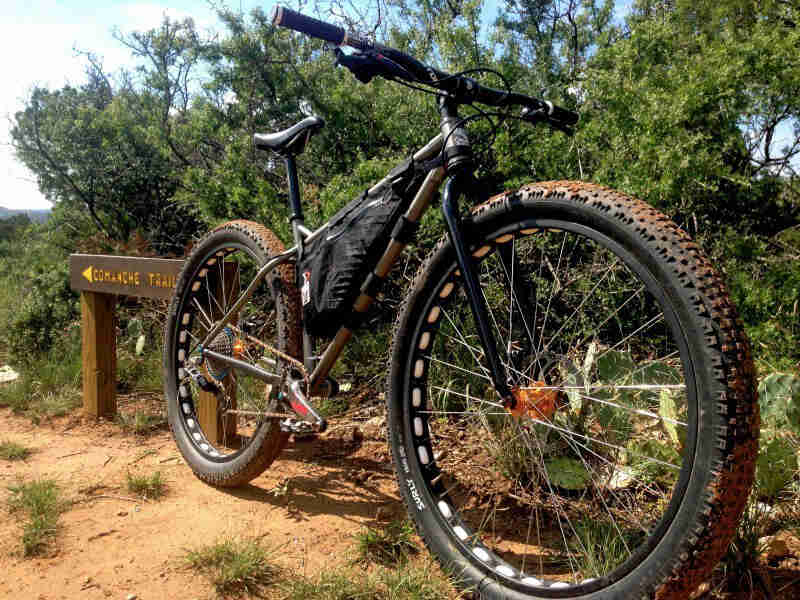 Front right side view of a Surly Krampus bike, parked on desert trail, in front of small cactuses and trees