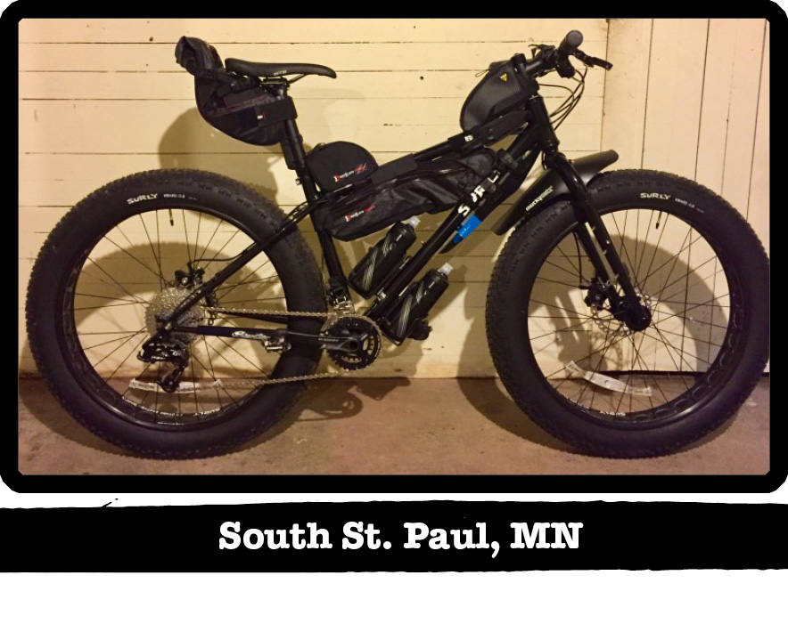 Right profile view of a Surly fat bike, loaded with gear, leaning on a painted wood wall-South St. Paul, MN banner below image