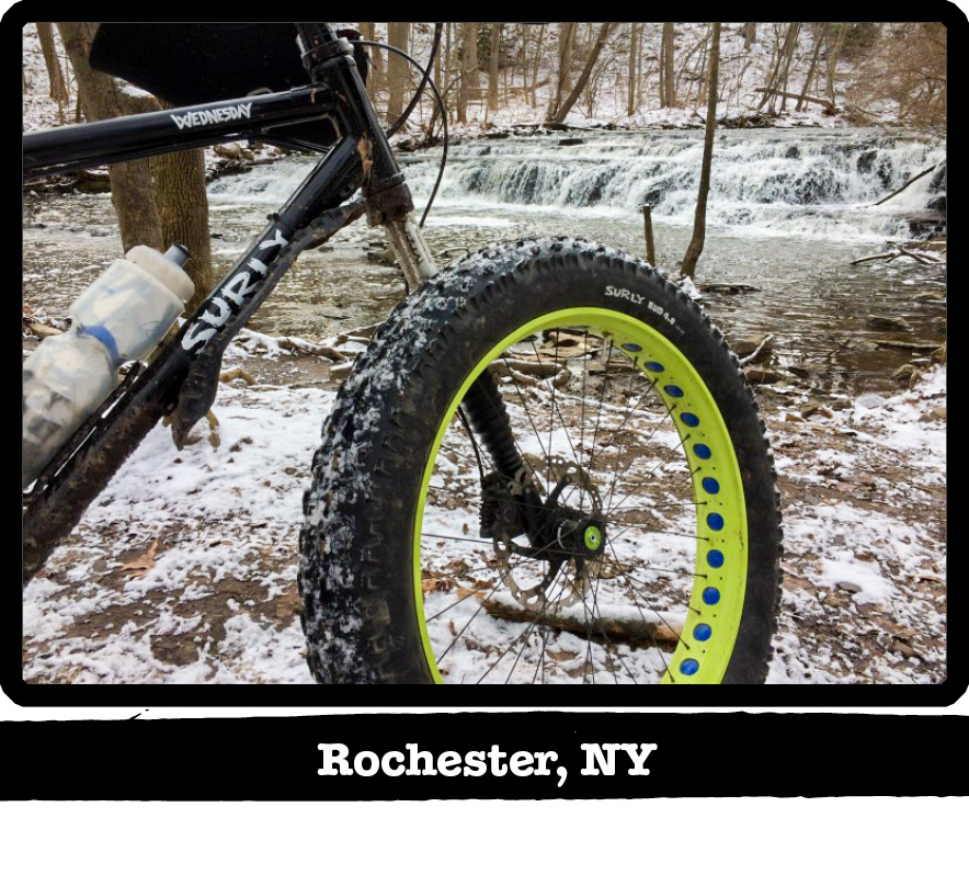 Right side front end view of a Surly Wednesday fat bike on snow in front of a waterfall-Rochester, NY banner below image