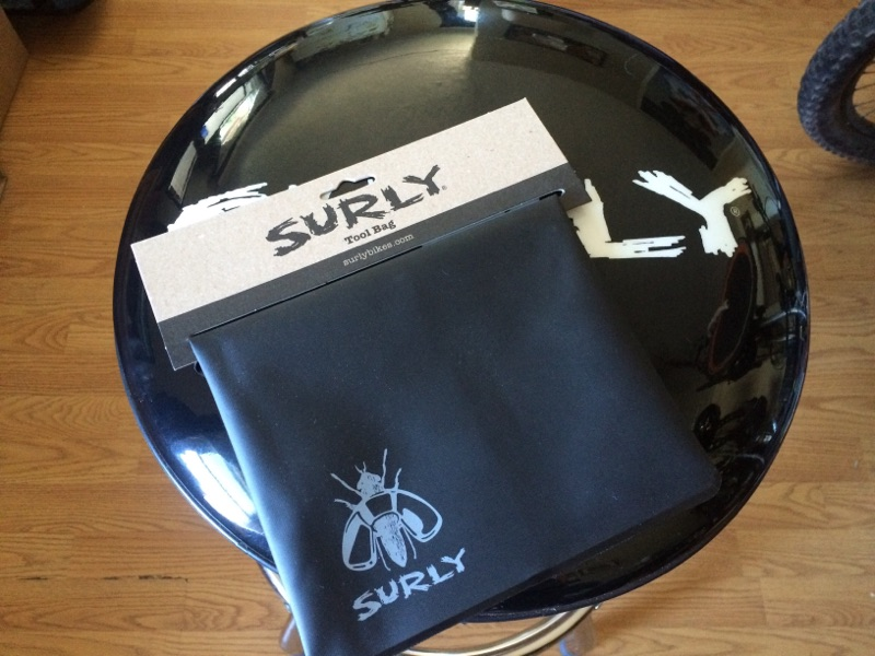 Downward view of a Surly tool bag, black, on a barstool seat
