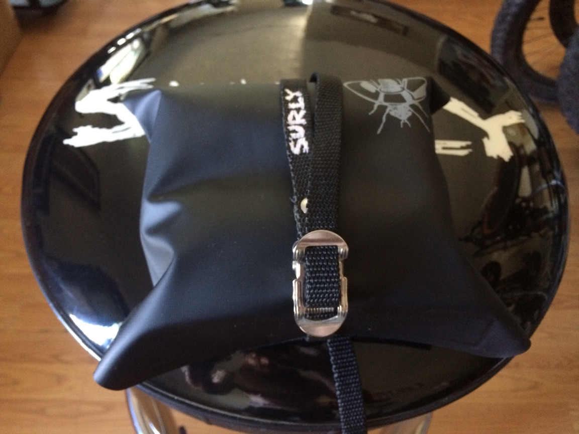 A Surly tool bag, black, packed with gear, with a strap wrapped around it, on top of a barstool seat