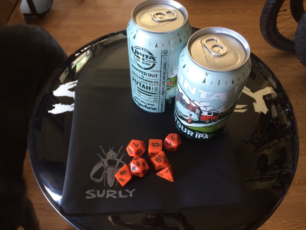 A Surly tool bag, black, with 2 beer cans and game pieces, on top of a barstool seat