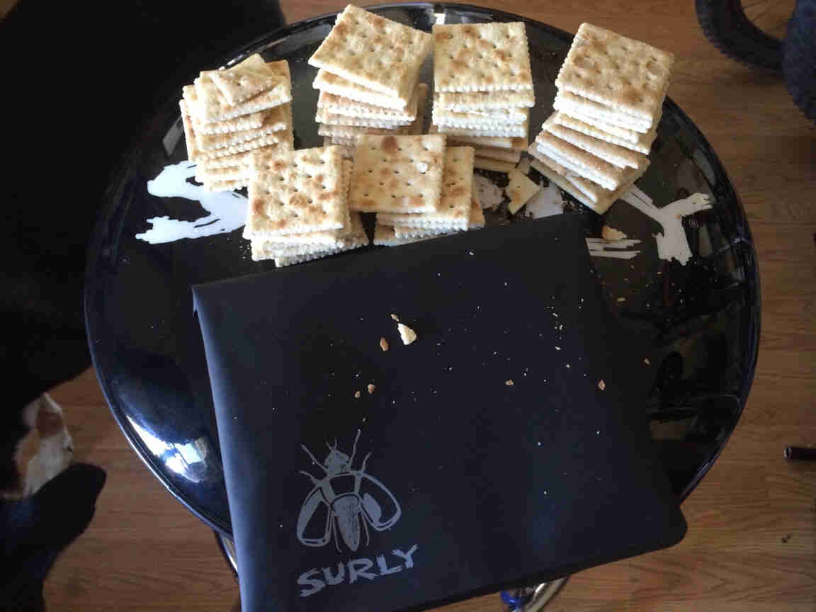 A Surly tool bag, black, with stacks of saltine crackers, on top of a barstool seat