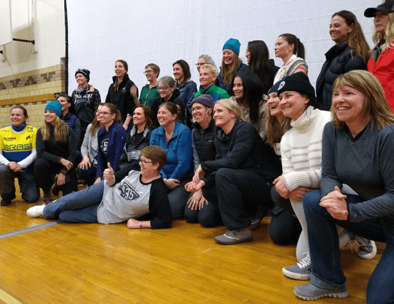 Angled view of a group of smiling bike race participants pose for a picture in a gymnasium