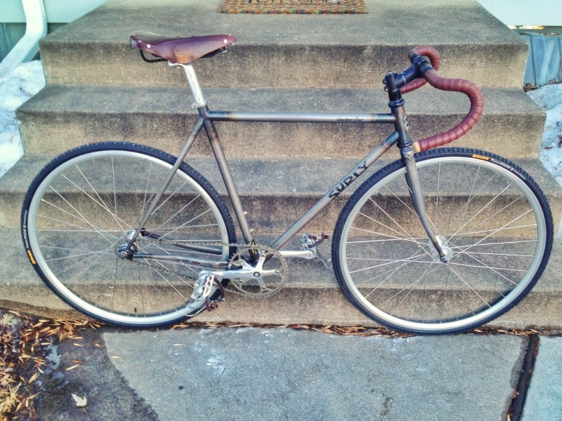 Right side view of a Surly Steamroller bike, parked at the bottom of a set of cement steps, below a front porch
