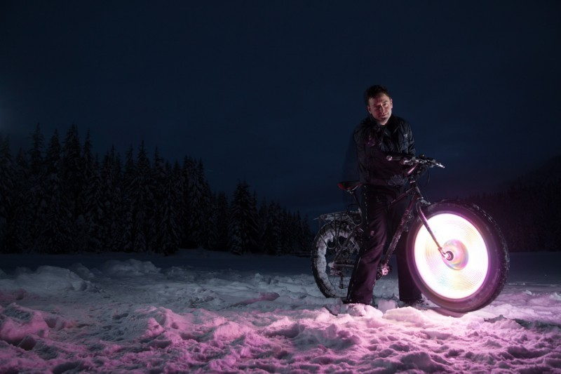 Right side view of a Surly fat bike, with a lit up front wheel, and cyclist standing over, on a snowy field at night