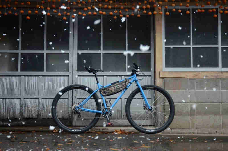 Right profile view of a blue Surly bike on pavement, in front of a building with windows, with snow falling