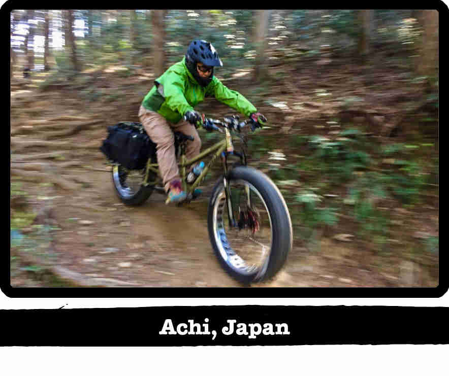 Right side view of a cyclist riding a Big Fat Dummy bike down a wooded, dirt trail hill - Achi, Japan tag below image