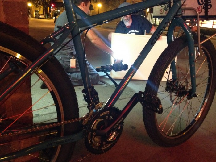 Low, right side view of a blue Surly bike, parked on a sidewalk, with 2 people kneeling with a light & camera, at night