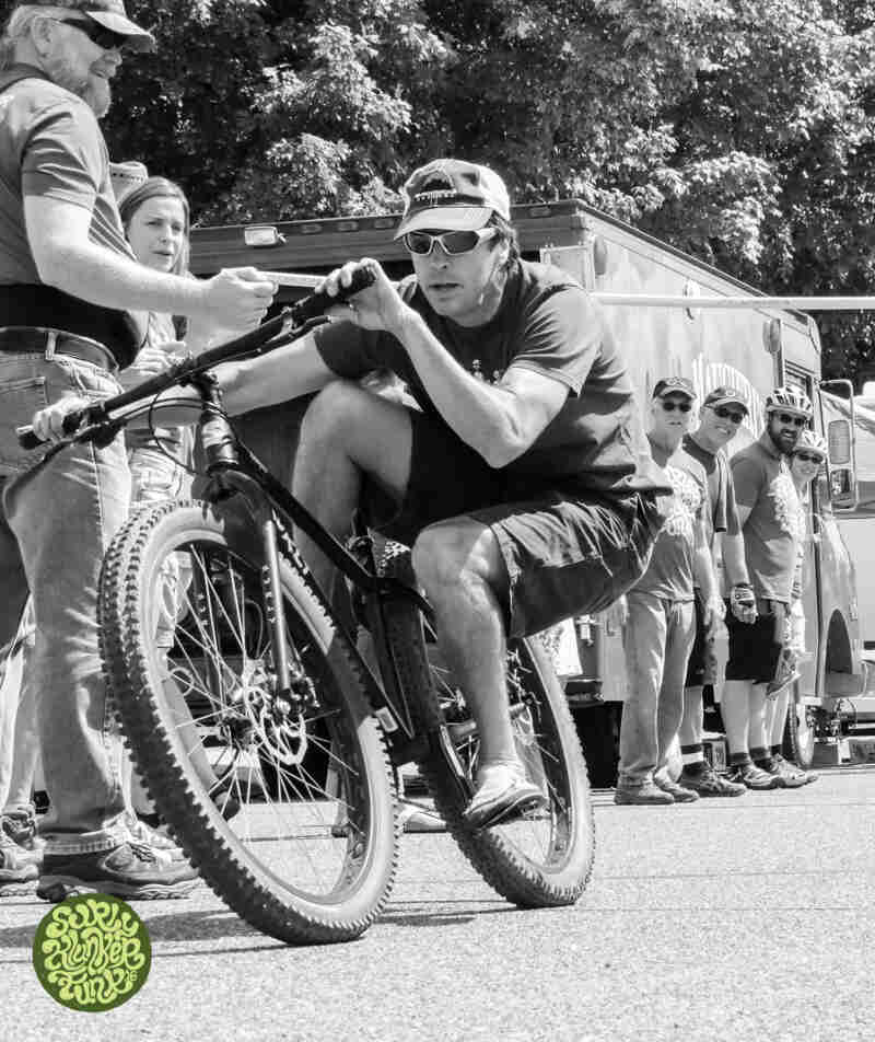 A cyclist riding a bike, seated low, new the back tire - black and white image