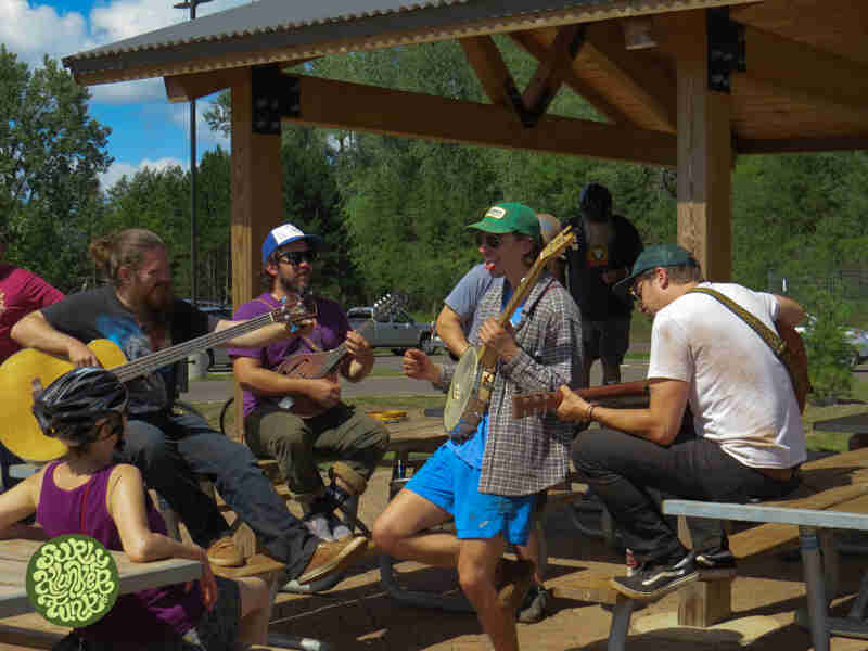 A group of musicians playing instruments, while sitting on picnic tables, under a park shelter