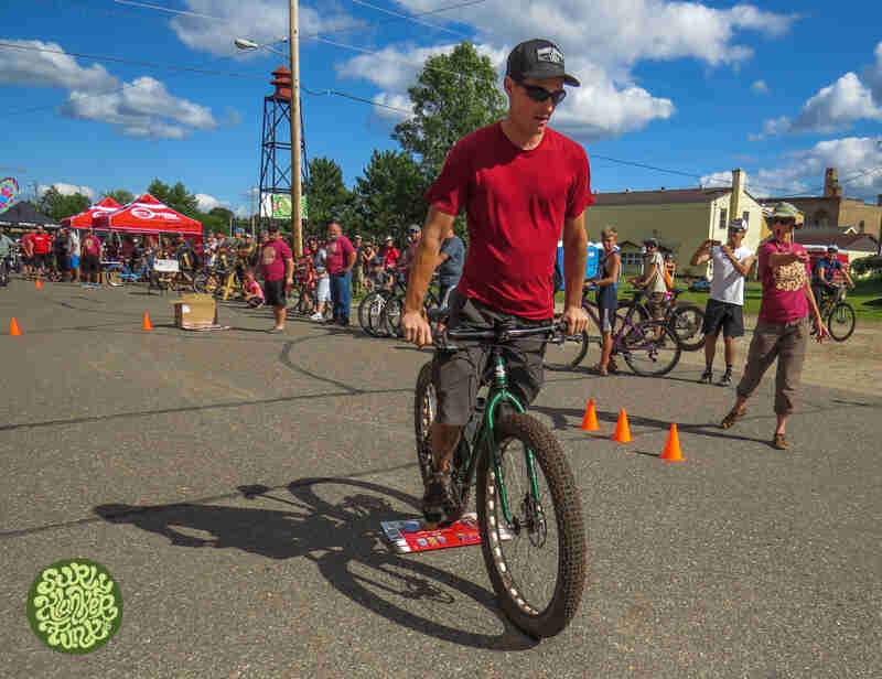 Front view of a cyclist riding a Surly Krampus bike, green, during a contest, with spectators watching in the background