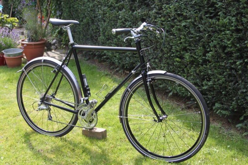 Right side view of a black Surly bike with fenders, parked in a grass yard, next to hedge bushes
