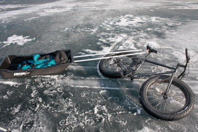 Right side view of a black Surly Moonlander fat bike, laying on it's side with a trailer sled attached, on an icy area