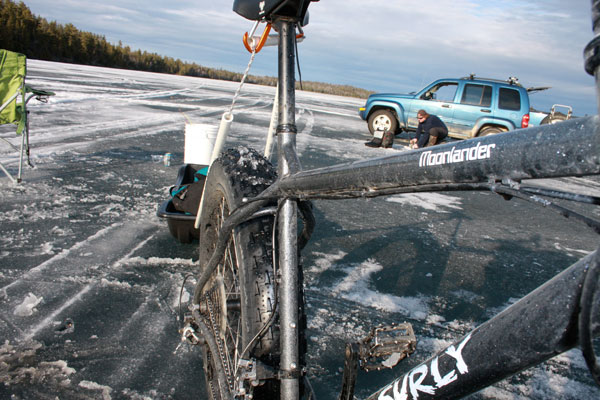 Front, right side view of a Surly Moonlander fat bike with a trailer sled behind it, standing on a frozen lake