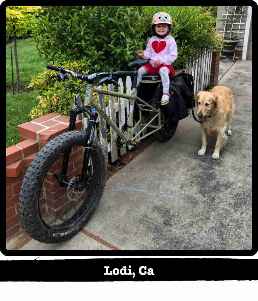 Left front view of a child sitting on the back of a Surly Bike Fat Dummy bike - Lodi, CA tag below image
