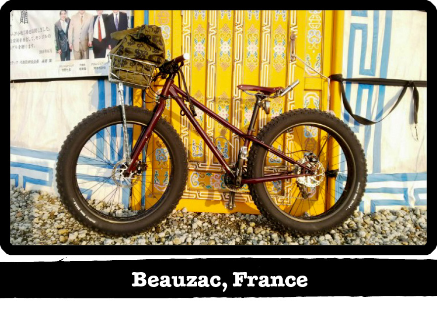 Left profile of a dark red Surly fat bike leaning a a colorful wall on gravel-Beauzac, France banner below image