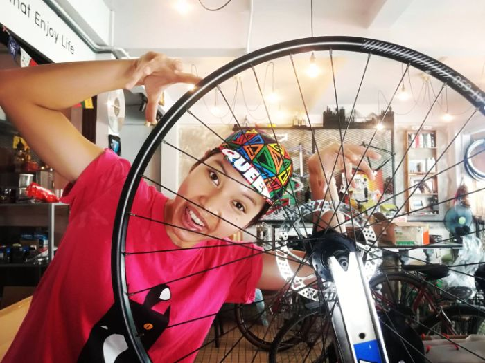 Immu building a bicycle wheel on a truing stand