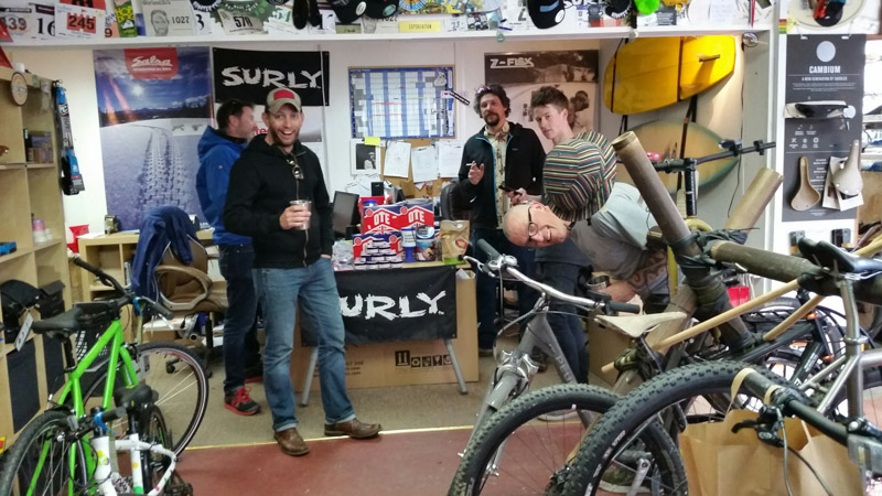 A group of five people stand in a shop with bike and a Surly banner