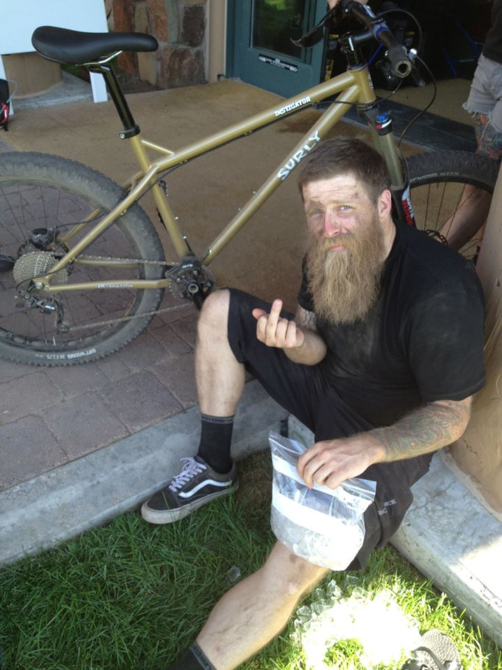 Downward view of a person, sitting in front of a Surly Instigator bike, icing their knee and showing their middle finger