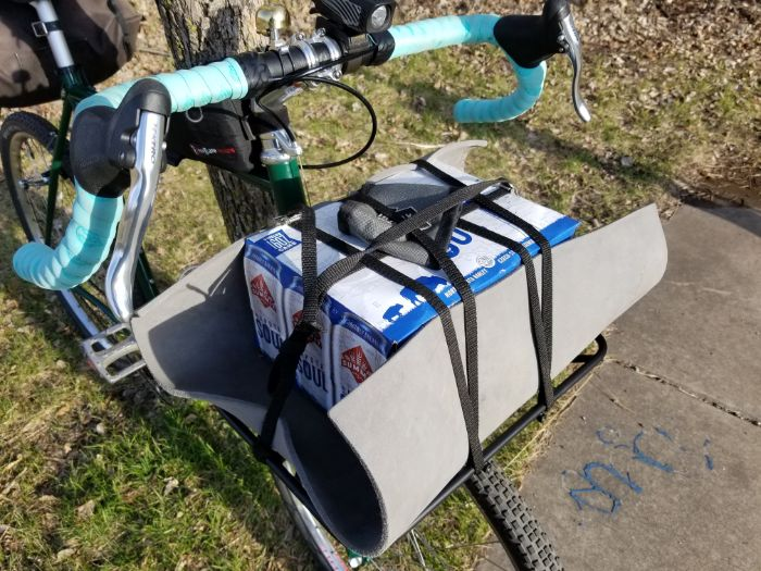 Downward view of a green Surly Pack Rat bike with front rack carrying a 12 pack of beer and Surly can cooler