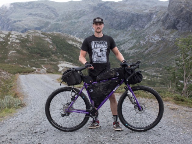 Cyclist poses while standing with a purple Surly bike on a gravel road in the mountains