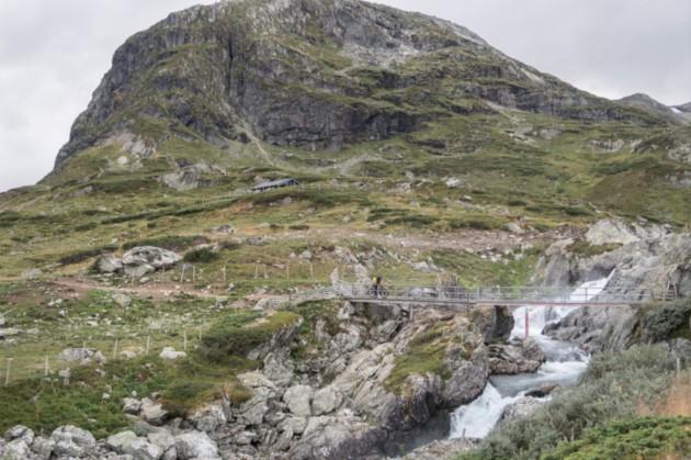 Person riding across a bridge over stream flowing down a mountain