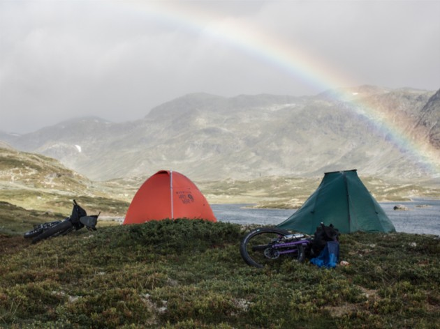 Two tents and two bike laying on a rocky grass clearing in the mountains with a rainbow arching over