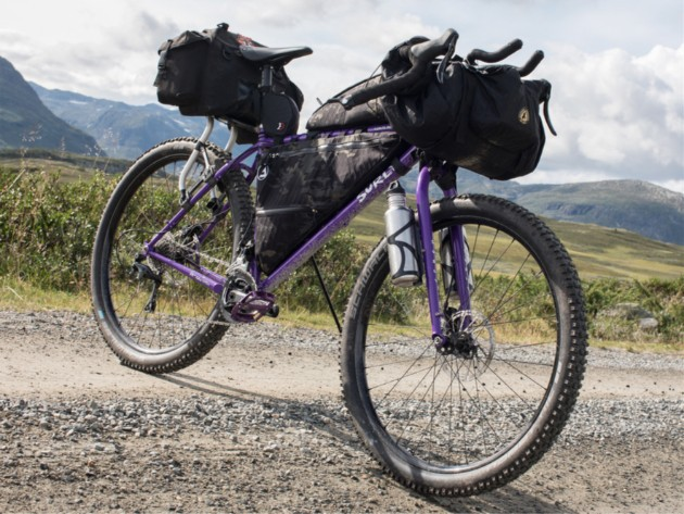 Front view of purple Surly bike loaded with gear standing across a gravel road in the mountains