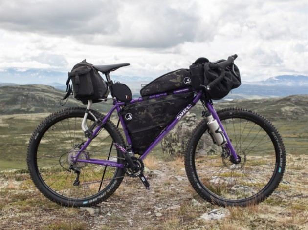 Right side view of a purple Surly bike loaded with gear stands on a grass and rock field in the mountains
