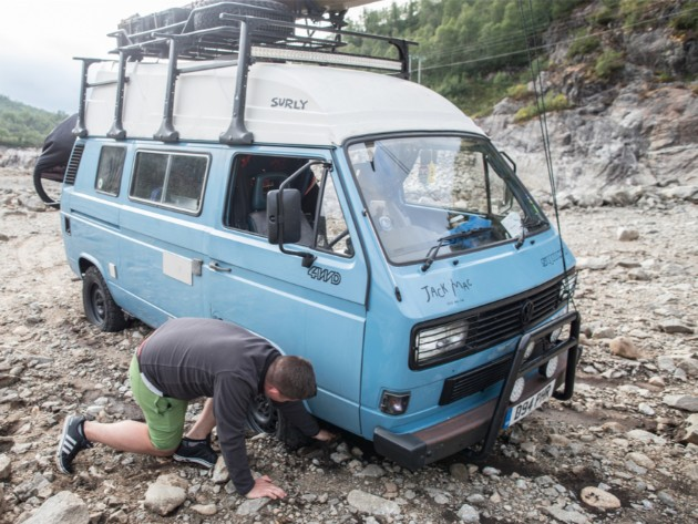 Person bending down next to a flat right front tire of a light blue VW van in a rocky environment