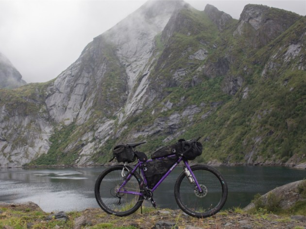 Right side view of a purple Surly bike on the edge of a lake in the mountains