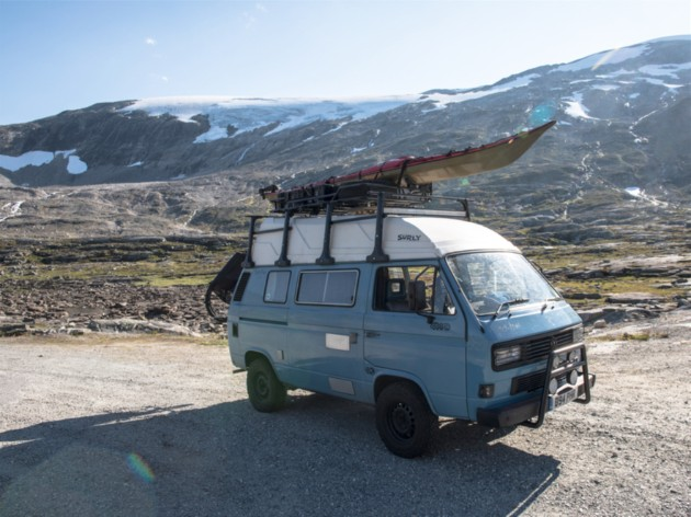 A light blue VW van with kayak on the roof rack drive on a gravel road in the mountains