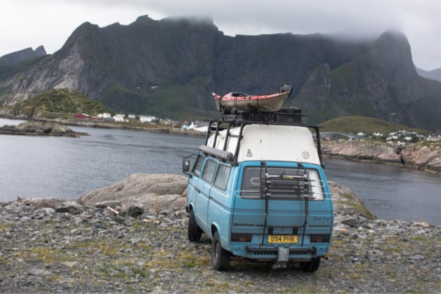 Rear view of a light VW van with a kayak on top, facing a river in the mountains
